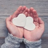 Woman holding two white love hearts. A woman is holding them in her hands. There is a rustic wood table underneath her hands. Valentines day or anniversary concept. Copy space.